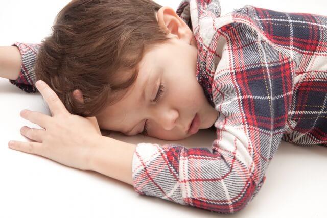 眠くて居眠りしている男の子